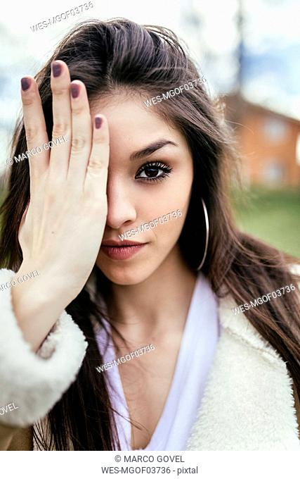 Portrait of a beautiful brunette woman covering an eye
