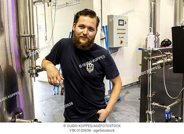 Tilburg, Netherlands. Portrait of Robin, a male beer brewer inside his newly build city brewery at Stadsbrouwerij 013. Locally produced craftbeers are booming