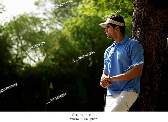 Golfer leaning against a tree