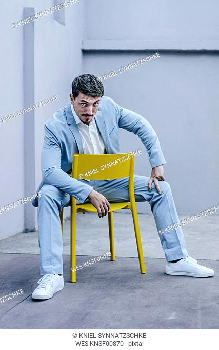 Portrait of confident businessman sitting on yellow chair