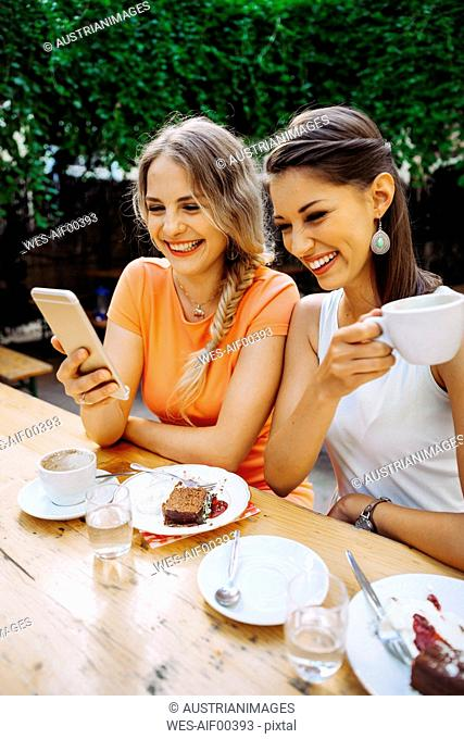 Two young women with cell phone picture at outdoor cafe