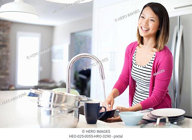 Happy young woman washing dishes in kitchen