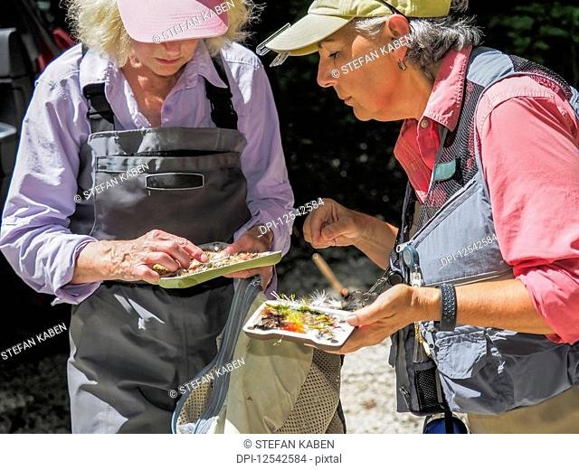 Women sorting lures for fly fishing, Gunpowder Falls River; Parkton, Maryland, United States of America