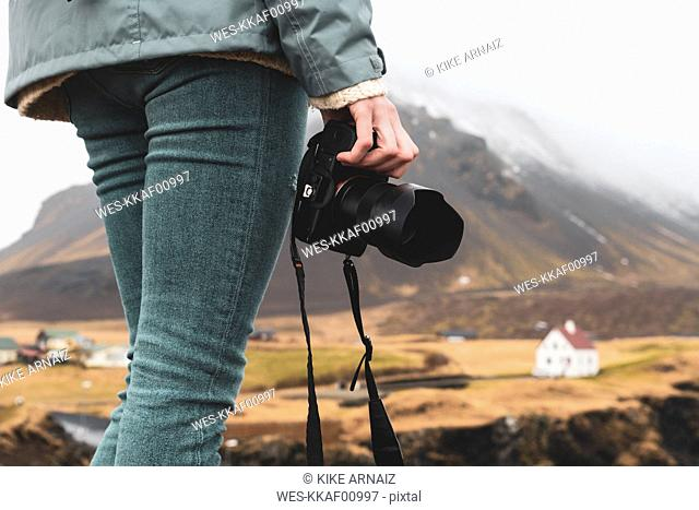 Iceland, woman with camera, partial view