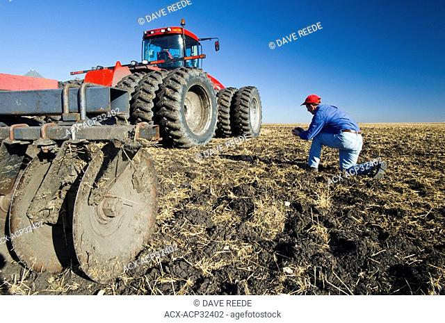 a man examines newly cultivated soil and wheat stubble beside a tractor pulling cultivating equipment near Lorette, Manitoba, Canada