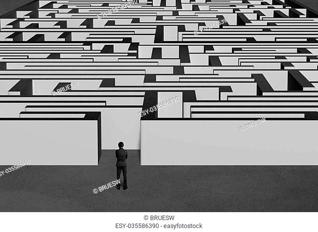 Businessman standing and facing huge maze structure with concrete background
