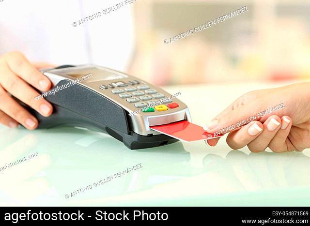 Close up of a client hands paying with credit card reader on a counter in a pharmacy