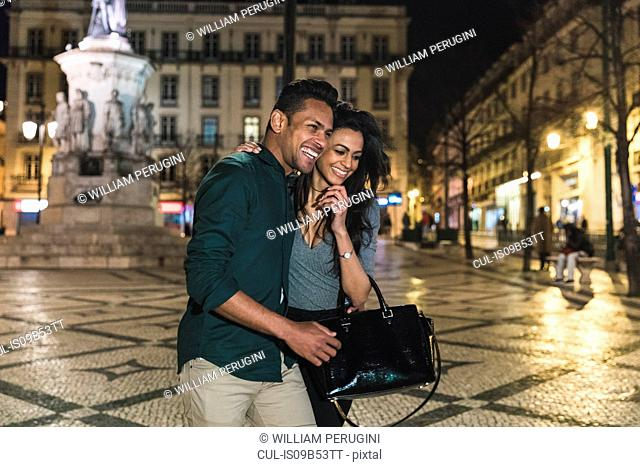 Couple walking through city, at night, Lisbon, Portugal