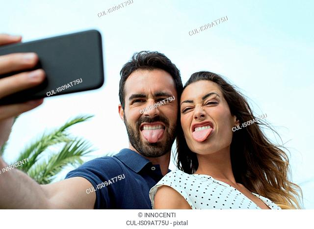 Young couple sticking out tongues for smartphone selfie