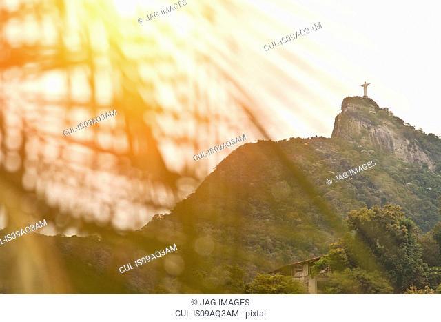 Christ the Redeemer Statue seen through palm fronds at sunset, RIo, Brazil
