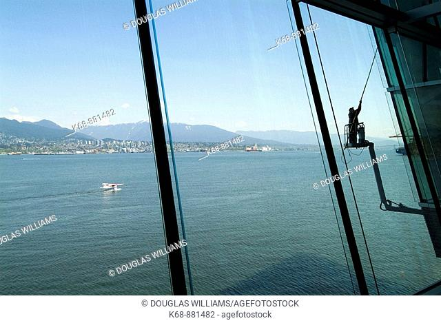 a window washer cleans windows at the Vancouver Convention Centre, Vancouver, BC, Canada. View of the port of Vancouver