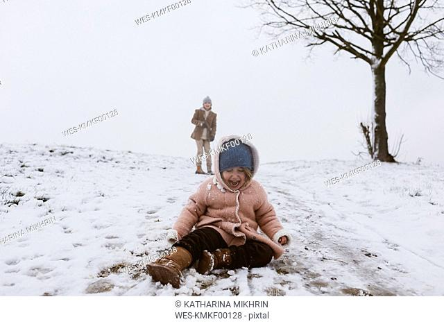 Crying girl on snow-covered meadow with brother in background