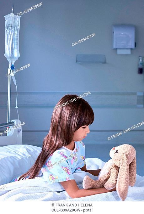 Girl patient gazing at toy rabbit on hospital children's ward