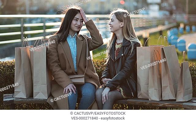 Asian girl showing latest purchase to her friend