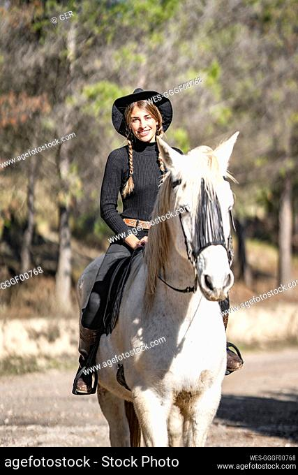 Portrait of woman horseback riding in paddock