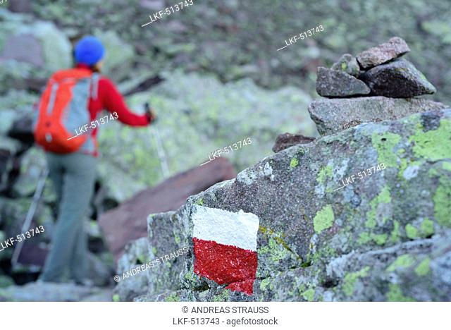 Woman hiking between boulders with rocks with trail marker and cairn in foreground, Trans-Lagorai, Lagorai range, Dolomites