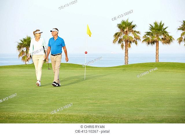 Senior couple walking on golf course