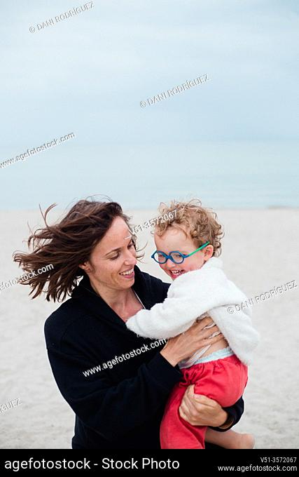 2 years old boy playing with his mother at the beach