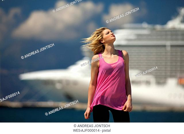 Greece, Young woman posing in front of cruise ship