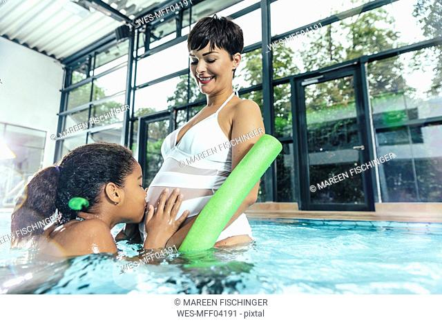 Girl kissing belly of her pregnant mother in indoor swimming pool