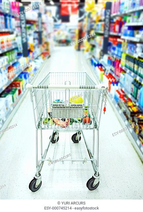 Closeup of a shopping trolley in aisle of supermarket