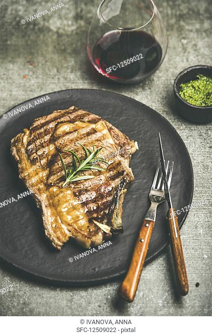 Grilled hot rib-eye beef steak on bone with chimichurri green sauce