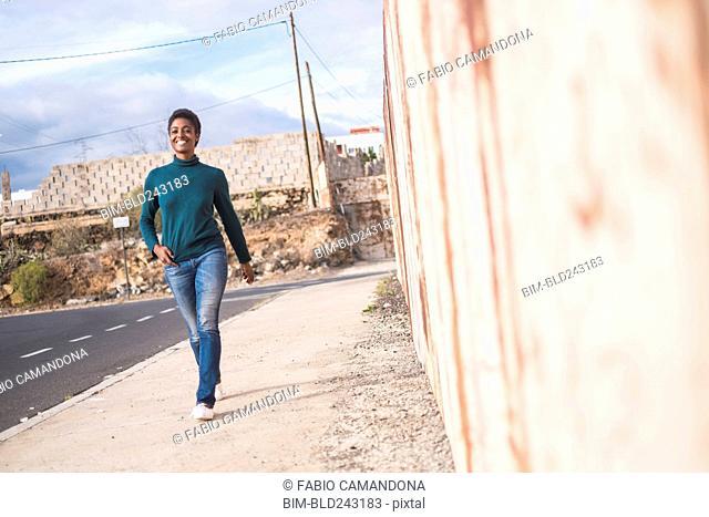 African American woman walking on urban sidewalk