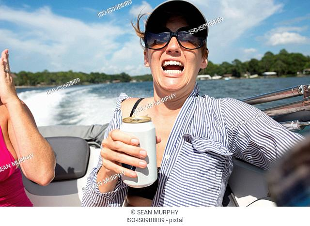 Woman on speedboat, holding beer, shocked expression