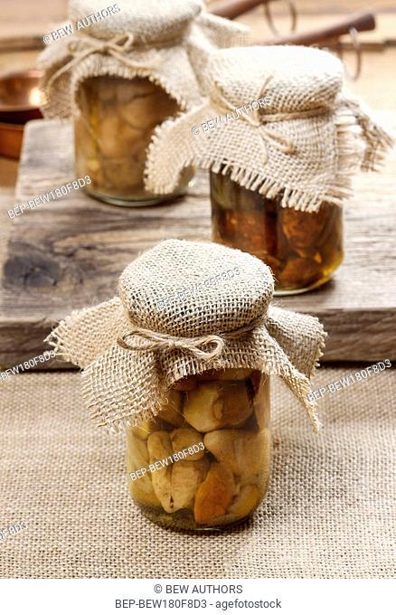 Pickled mushrooms in transparent glass jar