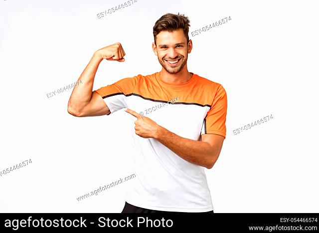 Guy brag with muscles asking if you want touch or gain such good body shape yourself. Sassy smiling, satisfied sportsman show biceps