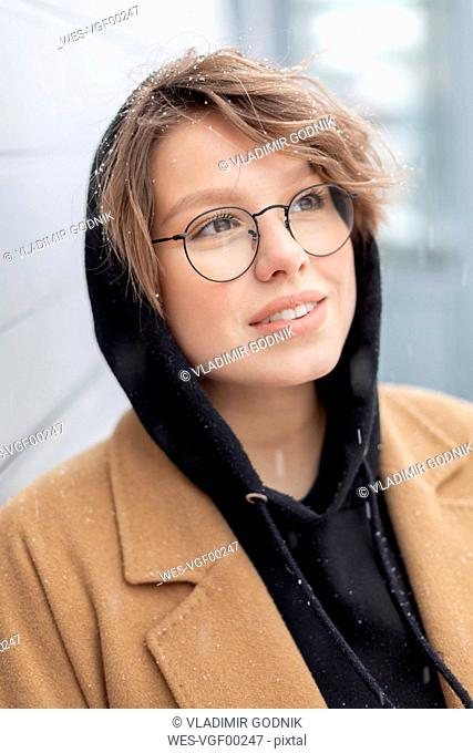Portrait of young woman at snowfall