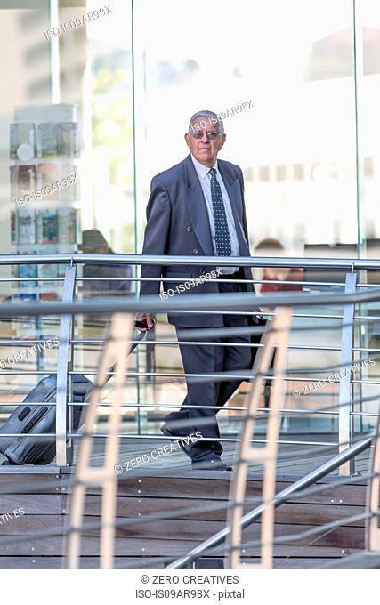 Senior businessman leaving hotel with wheeled suitcase