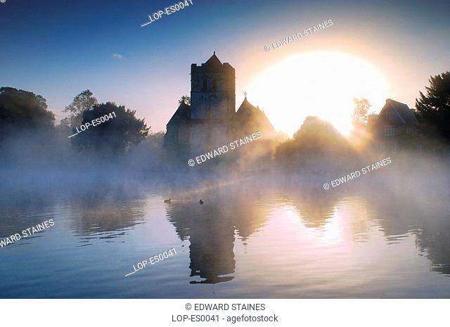England, Buckinghamshire, Bisham, Bisham Church in the early morning mist with ducks. Bisham is home to one of the Sport England's National Sports Centres