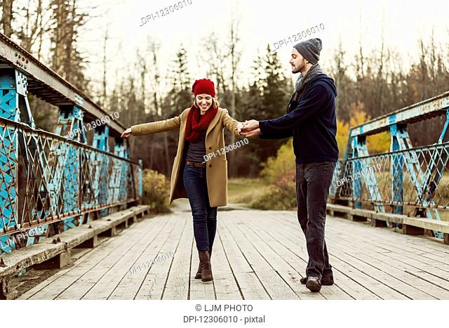 A young couple pretending to dance on a bridge in a city park in autumn; Edmonton, Alberta, Canada