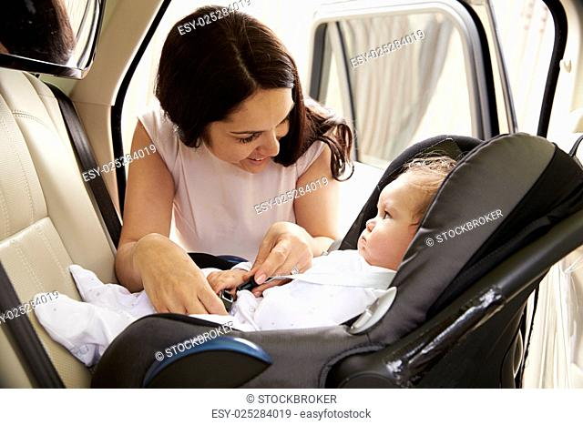 Mother Putting Baby Son Into Car Travel Seat