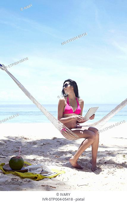 A young woman sitting in a hammock by the beach