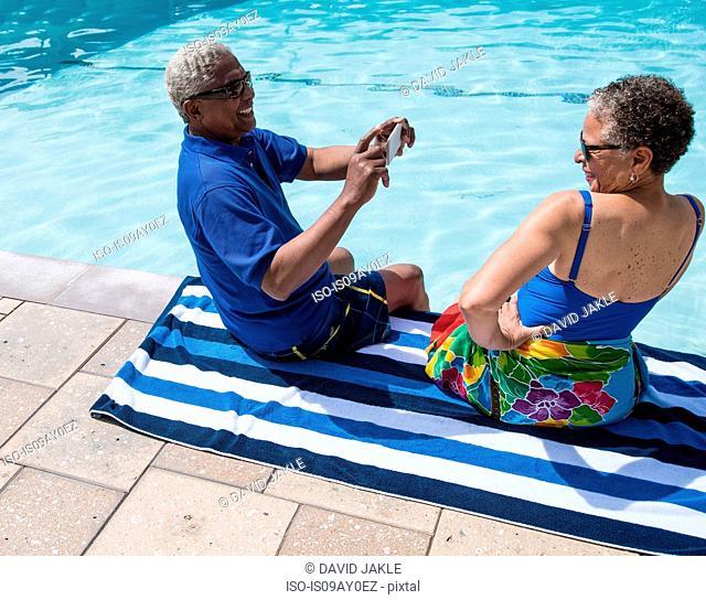 Senior couple sitting beside swimming pool, man taking photograph of woman using smartphone