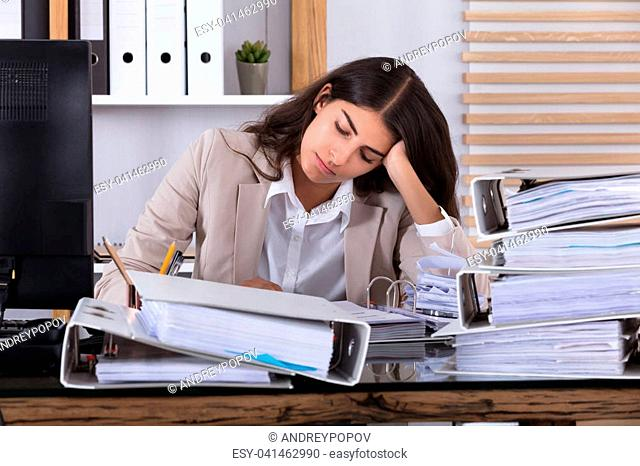 Stressed Young Businesswoman Working At Office With Stack Of Folders On Desk In Office