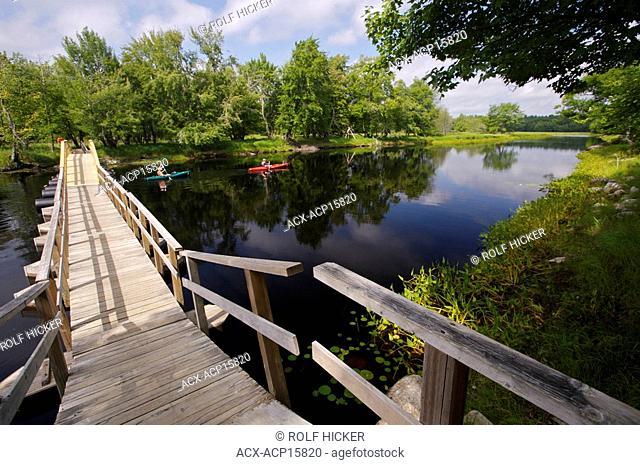 Foot bridge and kayakers on the Mersey River in Kejimkujik National Park and National Historic Site of Canada, Kejimkujik Scenic Drive, Highway 8, Nova Scotia