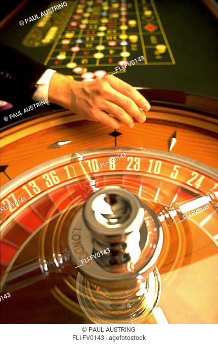 Roulette table with hand about to roll the dice vertical
