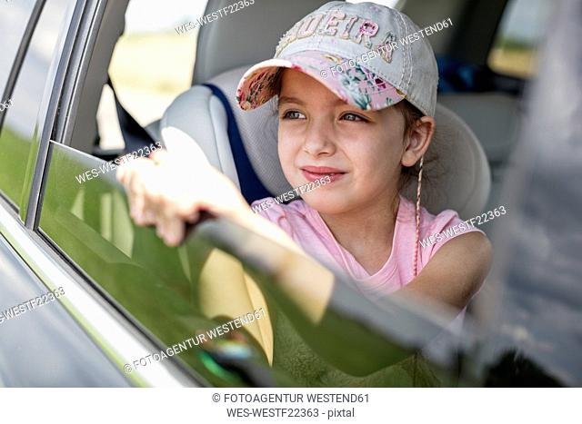 Girl sitting in car, looking out of window