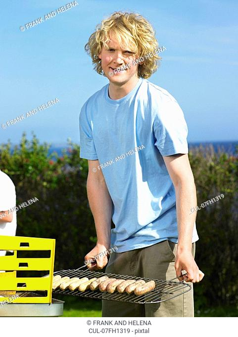 Man with sausages next to barbecue