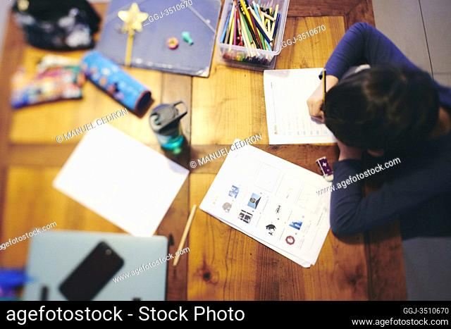 A boy doing homework during the coronavirus crisis. Following the closure of schools due to the corona crisis, school kids do a number of activities during...
