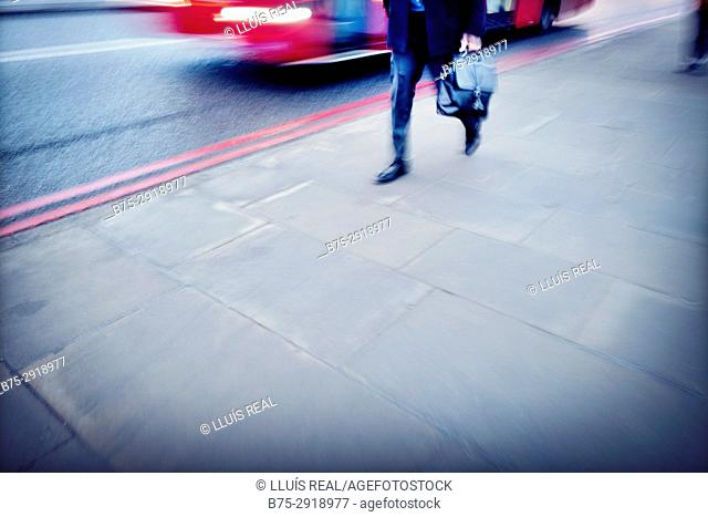 Legs of unrecognizable businessman with portfolio walking down in the street in the City of London, England, UK