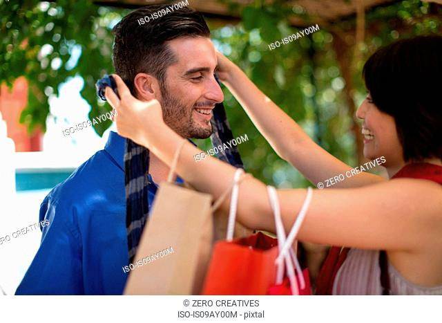 Young female shopper gifting boyfriend new tie in city
