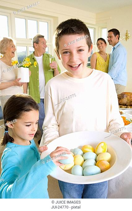 Boy and girl with bowl of Easter eggs