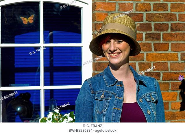 young woman with hat standing in front of a house smiling, Germany