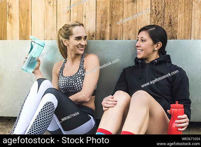 Female friends holding water bottle talking while resting against wall