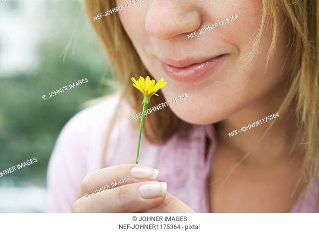 Close up of woman smelling yellow flower
