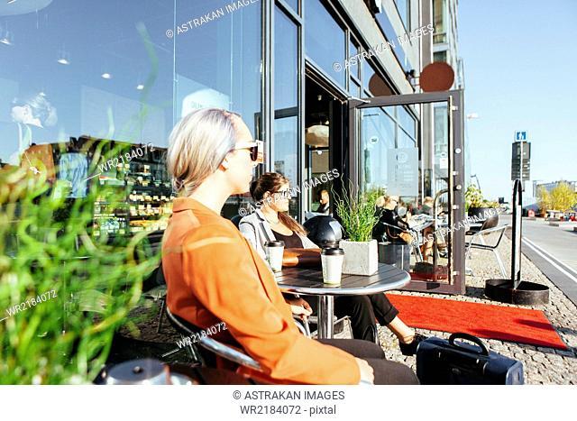 Businesswomen looking away while sitting at sidewalk cafe